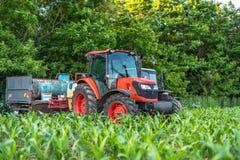 培养领域的红色拖拉机在蓝天下 免版税库存照片