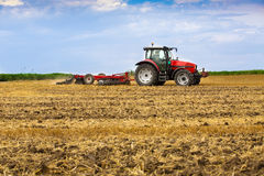 培养麦子亩茬地,庄稼残滓的拖拉机 免版税图库摄影