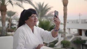 基于一种热带手段和打视频通话的愉快的白种人资深妇女 使用一个智能手机 t 影视素材
