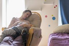 基于与婴孩睡觉的一把摇椅的疲乏的年轻母亲 免版税库存照片