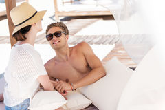 基于专辑的快乐的年轻的夫妇sunbed室外 图库摄影