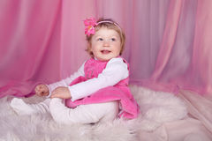 基于在桃红色布料商的床的愉快的微笑的滑稽的小女孩 免版税库存照片