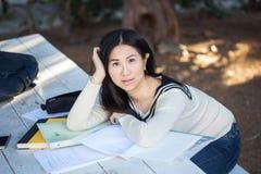 基于堆的一个美丽的年轻亚裔女孩笔记本与 免版税库存图片