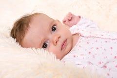 基于奶油色毛皮地毯的美丽的女婴 免版税库存照片