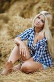 基于干草的性感的白肤金发的妇女在乡区 免版税图库摄影