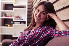 基于有休息的头的沙发的宜人地微笑的女孩  免版税库存图片
