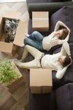 基于有箱子的沙发,顶视图的愉快的轻松的夫妇 图库摄影