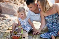 基于格子花呢披肩的愉快的家庭在海岸附近 库存照片