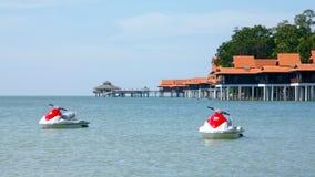 基于海的喷气机小船在假日别墅前 免版税库存图片