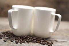 基于烤咖啡豆的两个杯子准备好早晨咖啡 库存照片