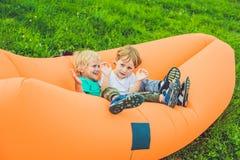 基于空气沙发的两个逗人喜爱的男孩在公园 库存照片