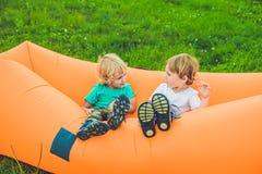 基于空气沙发的两个逗人喜爱的男孩在公园 图库摄影