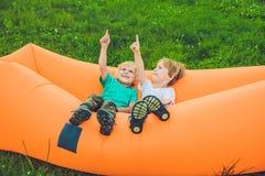 基于空气沙发的两个逗人喜爱的男孩在公园 免版税库存图片