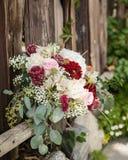 基于老木篱芭的深红,奶油色和绿色新娘花束 库存照片
