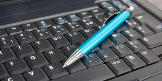 基于膝上型计算机键盘的蓝色圆珠笔 库存图片
