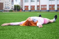 基于草的美丽的运动的红发女孩在体育以后 库存图片