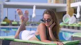 基于轻便马车休息室的太阳镜和游泳衣的时髦的可爱的女孩由游泳池边在昂贵的手段在期间 股票录像