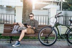 基于长凳和使用片剂通信连接数字式设备技术概念的年轻人骑自行车者 库存图片