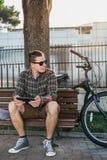基于长凳在夏天公园和使用片剂通信连接数字式设备技术概念的年轻人骑自行车者 免版税图库摄影