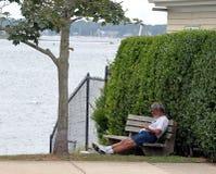基于长凳的一个人在水附近在纽波特,罗德岛 免版税库存照片