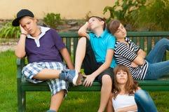 基于长凳的十几岁的男孩和女孩 库存照片