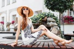 基于长凳的秸杆海滩帽子的时髦的美丽的妇女 免版税库存图片