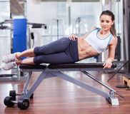 基于长凳的运动妇女在健身房 库存图片