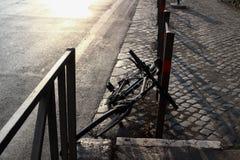 基于门的自行车,由导致与阳光泄漏的罗马罗马斗兽场意大利的路,在它后的 免版税库存照片