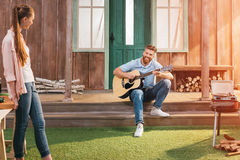 基于门廊的男人和妇女,使用在吉他的人 图库摄影