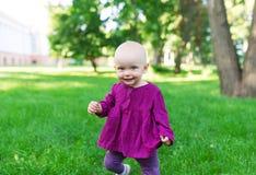基于绿草的愉快的婴孩 免版税库存图片