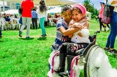 基多,厄瓜多尔2017年11月, 28日:关闭两chilldren,用泡沫盖的轮椅的小女孩,真实 图库摄影