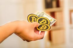 基多,厄瓜多尔- 2018年1月31日:妇女s的手室内看法许多举行与十dolla票据的金黄Bitcoins 免版税库存照片