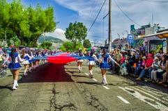 基多,厄瓜多尔- 2018年1月31日:学生grouo室外看法走和拿着与颜色的一面巨大的旗子  免版税库存照片