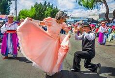 基多,厄瓜多尔- 2018年1月31日:室外观点的未认出的老人,跳舞的妇女穿一件桃红色礼服和  免版税库存图片