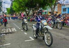 基多,厄瓜多尔- 2018年1月31日:的未认出的妇女穿警察制服和驾驶摩托车的室外观点 免版税库存照片