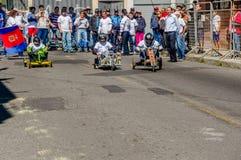 基多,厄瓜多尔- 2018年1月31日:的未认出的男孩赛跑在市街道的室外观点一辆木汽车基多 免版税库存图片