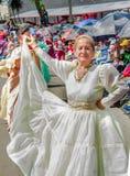基多,厄瓜多尔- 2018年1月31日:穿一件白色礼服和跳舞在街道的室外观点的美丽的老妇人 免版税库存照片