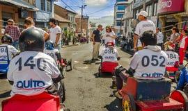 基多,厄瓜多尔- 2018年1月31日:赛跑在市街道的未认出的男孩一辆木汽车基多,后面看法 免版税图库摄影