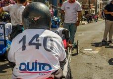 基多,厄瓜多尔- 2018年1月31日:赛跑在市街道的未认出的男孩一辆木汽车基多,后面看法 库存照片