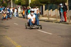 基多,厄瓜多尔- 2017年5月06日:赛跑在都市路的一个未认出的人一辆木汽车在城市里面街道  免版税库存图片