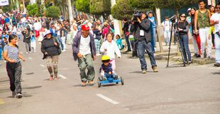 基多,厄瓜多尔- 2017年5月06日:赛跑在都市路的一个未认出的小男孩一辆木汽车在街道里面  免版税库存照片