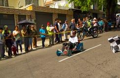 基多,厄瓜多尔- 2017年5月06日:赛跑在都市路的一个未认出的男孩一辆木汽车在城市里面街道  免版税图库摄影