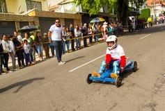 基多,厄瓜多尔- 2017年5月06日:赛跑在都市路的一个未认出的男孩一辆木汽车在城市里面街道  库存图片