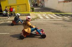 基多,厄瓜多尔- 2017年5月06日:赛跑在都市路的一辆木汽车的一对未认出的夫妇在城市里面街道  免版税库存照片