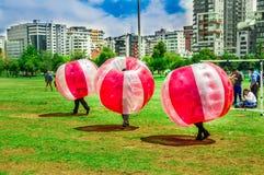 基多,厄瓜多尔- 2017年11月28日:踢足球的未认出的青年人,当是在巨型可膨胀的红色里面时 库存照片