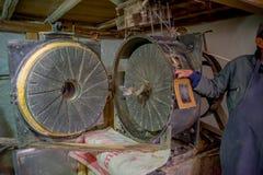 基多,厄瓜多尔- 2016年11月23日:递拿着一个老石研磨机磨房被做生产位于的面粉室内 免版税图库摄影