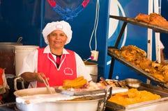 基多,厄瓜多尔2017年5月07日, :关闭准备hornado烤猪肉厄瓜多尔人的一名未认出的妇女传统 库存图片