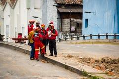 基多,厄瓜多尔- 2016年12月09日:一个未认出的小组愉快的消防队员` s队用在街道的设备 库存图片