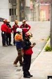 基多,厄瓜多尔- 2016年12月09日:一个未认出的愉快的消防队员` s队用在街道的设备 免版税库存照片