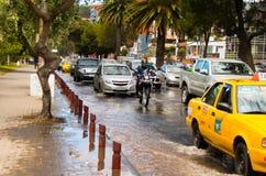 基多,厄瓜多尔- 2016年9月20日:一motocycle和汽车乘驾在一条被充斥的路在基多市在大雨以后 免版税库存图片
